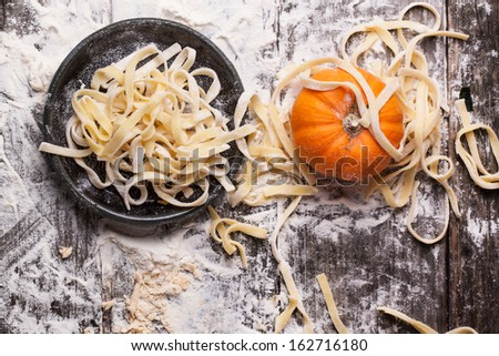 Top view on raw homemade pasta with pumpkin and flour over old wooden table. See series - stock photo