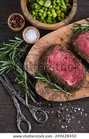 Top view on raw steak with herbs and pepper - stock photo