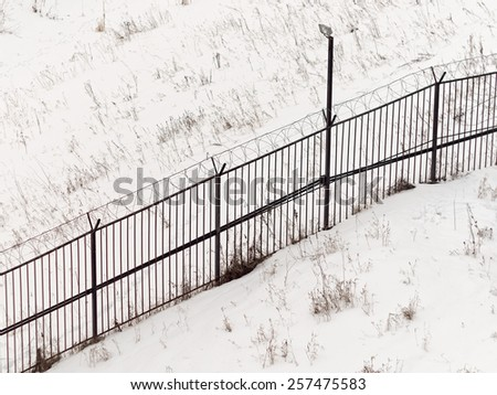 Top view on restricted bar fence of controlled area with razor barbed wire over it