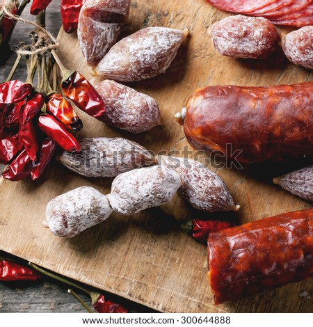 Top view on set of salami sausages served with red hot chili peppers on wooden cutting board. Square image. Top view - stock photo