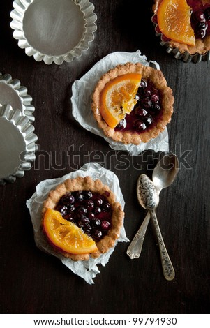 Top view on sweet fruit tartlets with fruit jelly and orange served with metal baking dish and spoons on black table - stock photo