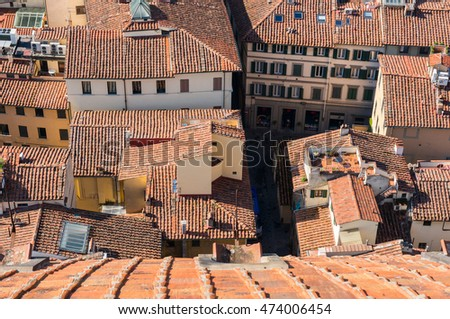 Top view on the red tiled roofs of old houses on narrow streets of historic center of Florence city, Italy