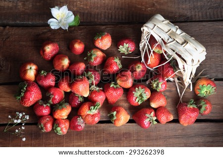 top view on the strawberry lying on a wooden table and scattered from the basket - stock photo