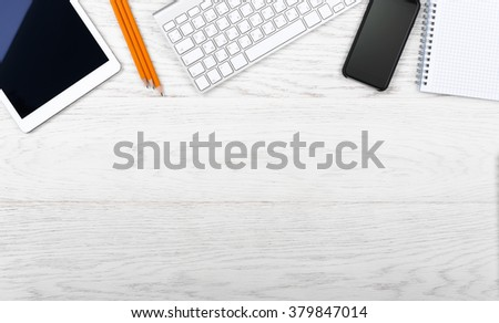 Top view on the workplace. Keyboard, tablet, smartphone and notepad on wooden table.  - stock photo