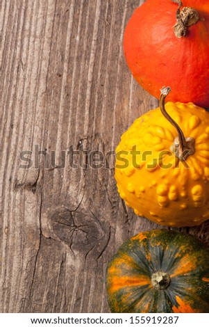 Top view on three colorful mini pumpkins on old wooden table
