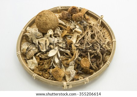 Top view on variety of dried mushrooms in a round bamboo tray.  Some of the mushrooms are straw mushroom, pholiota nameko, chinese wild hericium and velvet pioppini. Isolated on white background.