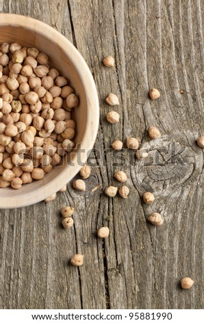 Top view on wooden bowl with Dry raw organic chickpeas on old wooden table - stock photo