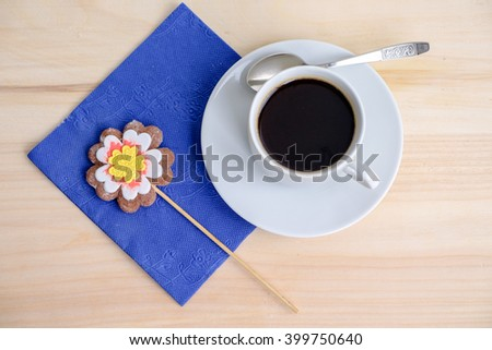 top view on wooden table with cup of coffee and blue napkin with cookies on wand