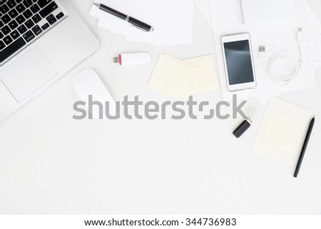 Top view on working desk with laptop and office equipment with blank space