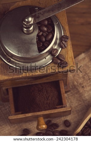 top view over old manual coffee grinder on wooden table