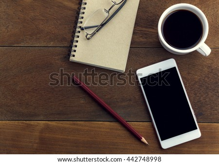 Top view pen,note paper,cup of coffee,smartphone or mobile phone,eyeglasses by business or technology background.