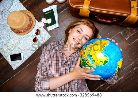 Top view photo of beautiful blonde girl lying on wooden floor. Young woman smiling, holding globe and looking at camera. Passport, tickets, mobile phone, hat, suitcase and map are on floor - stock photo