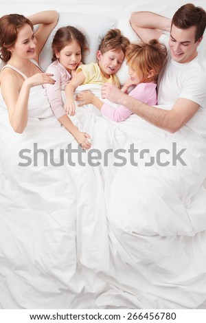 Top view photo of family of five under blanket on white bed early in the morning. They hugging each other. Children sleeping with their parents - stock photo