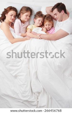 Top view photo of family of five under blanket on white bed. They hugging each other. Children sleeping with their parents - stock photo