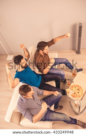top-view photo of happy cheerful men resting and watching tv - stock photo