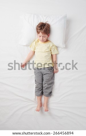 Top view photo of little cute boy sleeping on white bed. Quiet Soldier pose. Concept of sleeping poses - stock photo