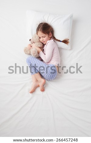 Top view photo of little cute girl sleeping on white bed with teddy bear. Quiet Foetus pose. Concept of sleeping poses - stock photo