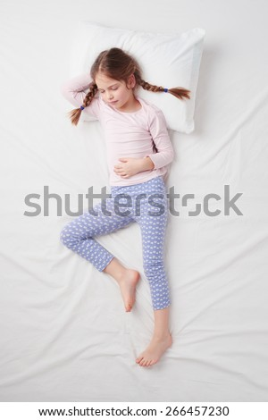 Top view photo of little cute girl with pigtails sleeping on white bed. Concept of sleeping poses - stock photo