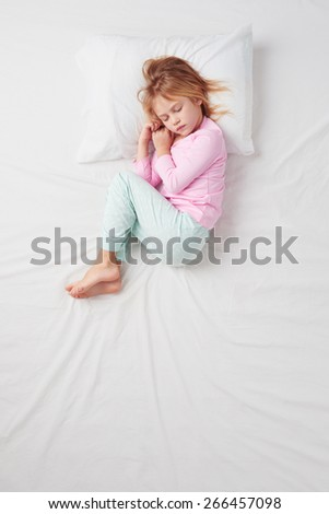 Top view photo of little girl sleeping on white bed. Quiet Foetus pose. Concept of sleeping poses - stock photo