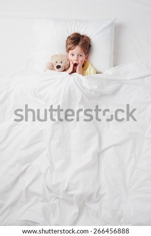 Top view photo of little scared boy under blanket with teddy bear. Concept for children's nightmares - stock photo
