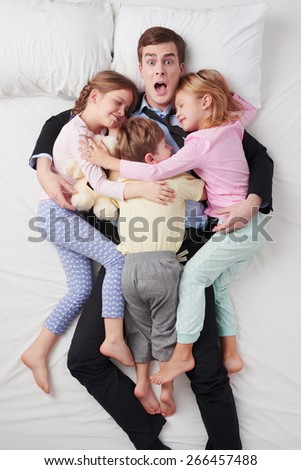 Top view photo of shocked businessman wearing suit, and his three children. Father's arms are over daughters and son. Children sleeping on father and hugging each other - stock photo