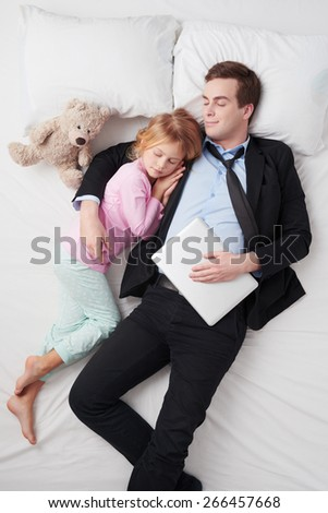 Top view photo of tired businessman holding laptop, and his little cute daughter. Father's arm is over daughter. They both sleeping on white bed - stock photo