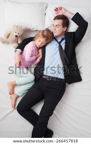 Top view photo of tired businessman wearing suit, and his little cute daughter. Father's arm is over daughter. They both sleeping on white bed - stock photo