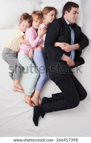 Top view photo of tired businessman wearing suit, and his three children. Father sleeping with his daughters and son on white bed - stock photo
