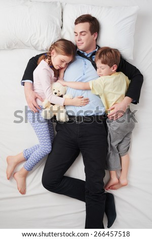 Top view photo of tired businessman wearing suit, and his two children. Father's arms are over daughter and son. They sleeping on white bed and hugging each other - stock photo