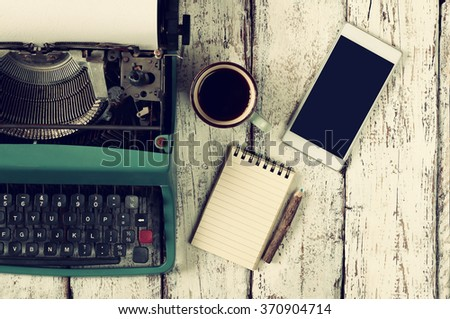 top view photo of vintage typewriter, blank notebook, cup of coffee and smartphone on wooden table. retro filtered image - stock photo