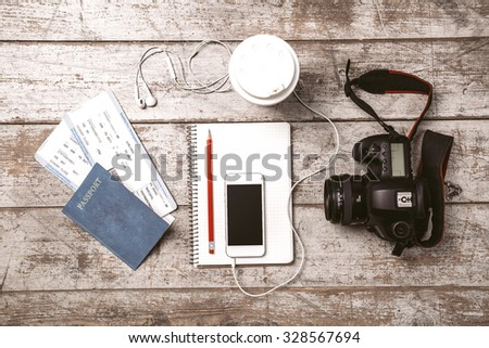 Top view photo of white mobile phone, professional camera, notebook, passport, tickets, pencil, cup and headphones. Objects are on light colored wooden floor - stock photo