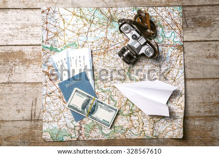 Top view photo of world map, white paper plane, passport, tickets, money and vintage camera. Objects are on light colored wooden floor - stock photo