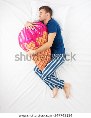 Top view photo of young man sleeping in an embrace with a large soft ice cream toy and dreaming of sweets - stock photo