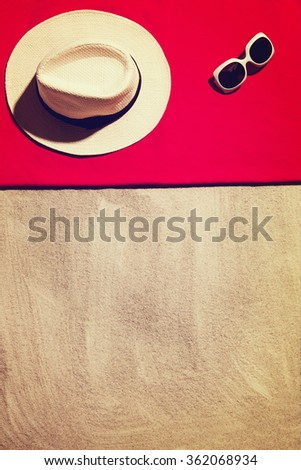 Top view photograph of sandy beach with summer accessories and copy space around objects. Vertical photo taken from above with visible sand texture. Vintage, retro effect processing. - stock photo