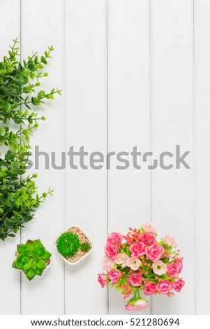 Top view photography of small flowers on white wood background.