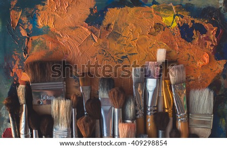 Top view picture of wooden paintbrush set different size with old palette on the background.  - stock photo