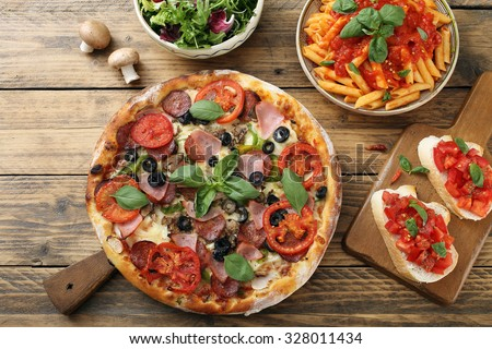 top view pizza pasta with tomato sauce and salad bowl on rustic table - stock photo