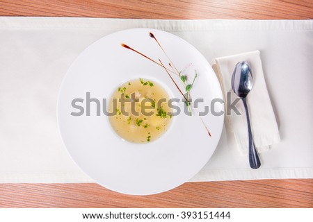 Top view Plate of Fresh chicken bouillon in the round white plate on the served restaurant table   - stock photo