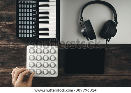 Top view portable travel music production set midi mixer control piano keyboard smartphone tablet retina laptop black dj headphones with leather earpad long twisted cort on aged table Hand twist knob - stock photo