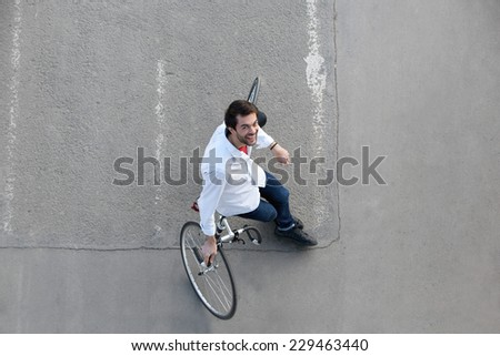 Top view portrait of a happy man relaxing with bicycle on street - stock photo