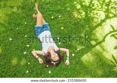 top view portrait of a pretty young woman relaxing on a grass - stock photo