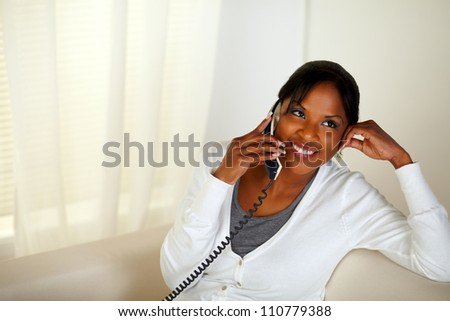 Top view portrait of a relaxed woman smiling and conversing on phone while sitting on couch at home indoor