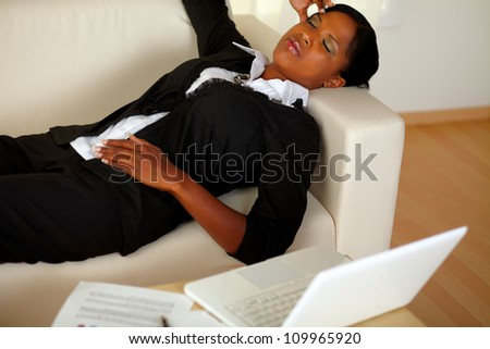 Top view portrait of a young executive woman lying on sofa with eyes closed and headache in front of her laptop - stock photo