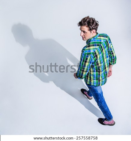 Top view portrait of a young man in colourful wear walking  over gray background - stock photo