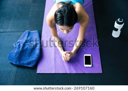 Top view portrait of a young woman doing yoga exercises on yoga mat at gym - stock photo