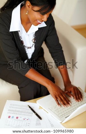 Top view portrait of an attractive businesswoman working on laptop on black suit while sitting on sofa - stock photo