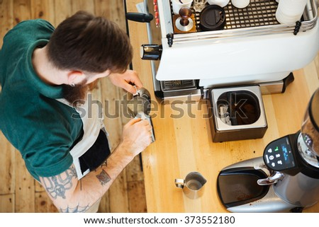 Top view portrait of barista pouring milk into cup of coffee at the coffee shop - stock photo