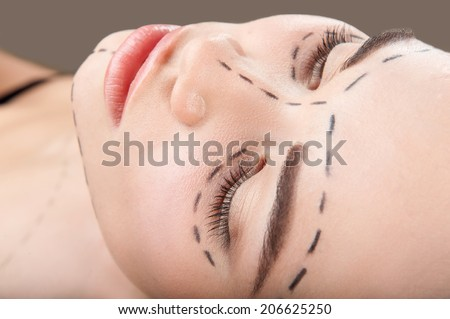Top view portrait of beautiful young woman with perforation lines around her eyes and chin looking up before plastic surgery operation isolated on grey - stock photo