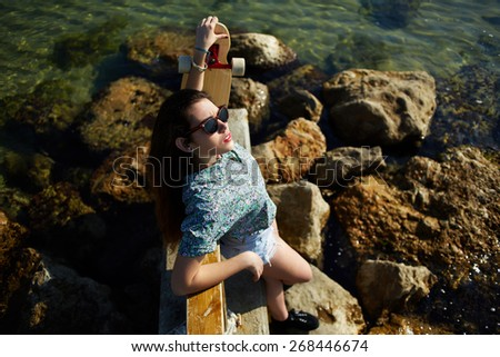 Top view portrait of cool young woman posing with her skateboard in front of the sea while enjoying summer sunshine, attractive hipster girl in sunglasses relaxing outdoors standing on rocks seashore - stock photo