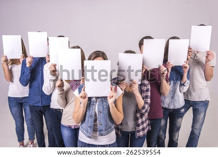 Top view. Portrait of four teenage group holding a white board and cover their faces. isolated on grey background. - stock photo
